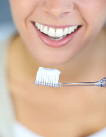 Closeup on womans toothy smile brushing her teeth photo