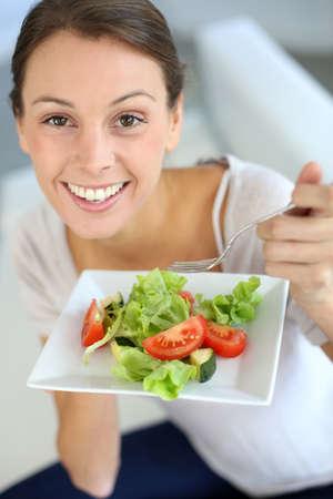 Closeup of cheerful woman eating fresh salad photo