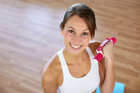Fitness girl lifting dumbbells in gym Stock Photo - 15611361