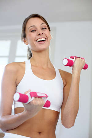 Fitness girl lifting dumbbells in gym photo
