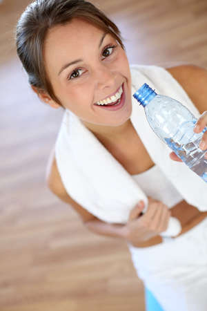 30 years old woman: Cheerful fitness girl drinking water after exercising