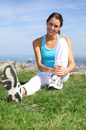 sitting on ground: Young woman doing stretching exercises outside