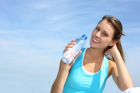 30 years: Thirsty fitness girl holding bottle of water