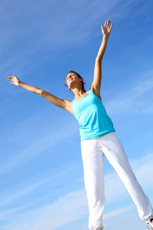 arms in air: woman doing yoga exercises in countryside Stock Photo
