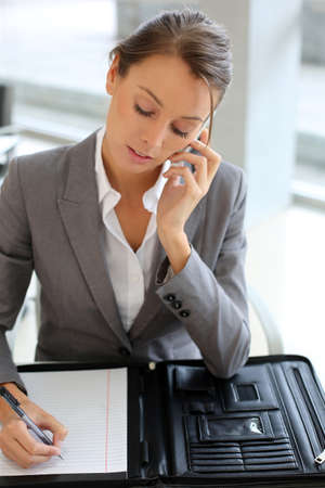 Business girl talking on the phone and taking notes Stock Photo - 15811196