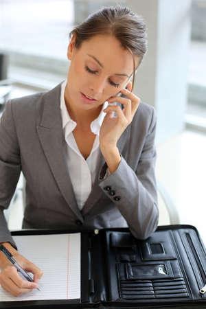 taking note: Ragazza affari parlando al telefono e prendere appunti