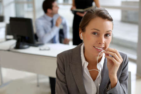 Businesswoman talking on mobile phone with handsfree device Stock Photo - 15811186