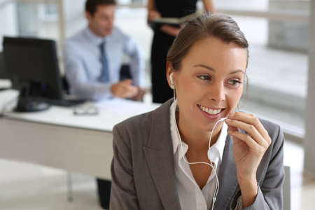Businesswoman talking on mobile phone with handsfree device Stock Photo - 15811151