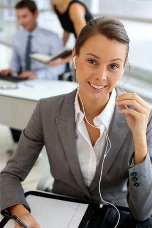 Businesswoman talking on mobile phone with handsfree device Stock Photo - 15811222