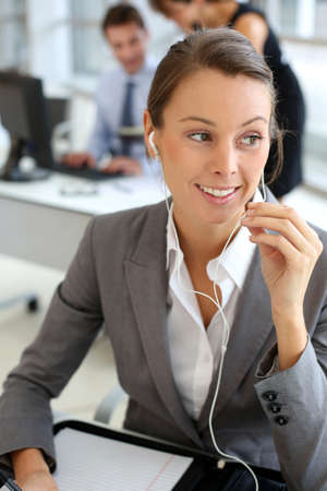 Businesswoman talking on mobile phone with handsfree device Stock Photo - 15811227