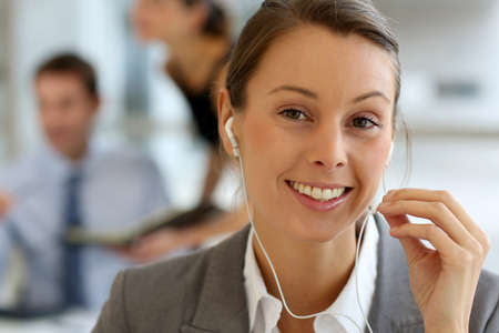 Businesswoman talking on mobile phone with handsfree device Stock Photo - 15811209