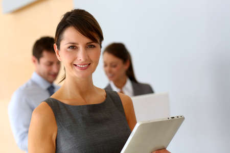 business woman standing: Businesswoman standing in corridor with tablet Stock Photo