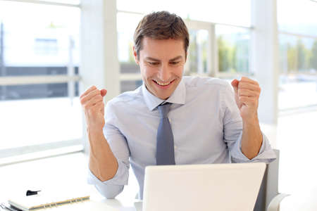 Businessman with successful expression in front of laptop photo