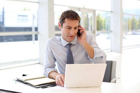 talking businessman: Retrato de hombre de negocios hablando por tel�fono m�vil en la oficina Foto de archivo