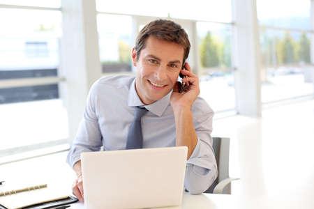 telephone salesman: Portrait of businessman talking on mobile phone in office