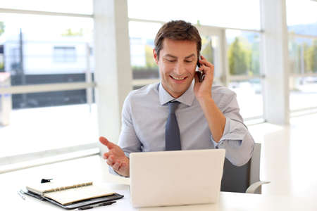 Happy businessman on the phone in front of laptop Imagens