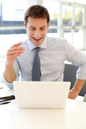 Businessman in front of laptop reading good news photo