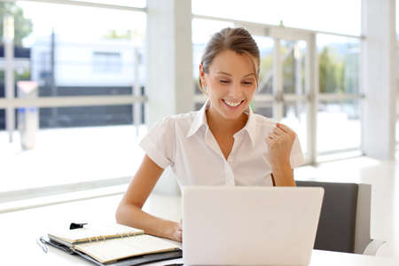 sit up: Cheerful office-worker showing thumbs up in front of laptop