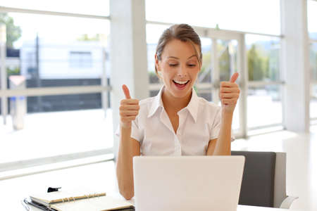 officeworker: Cheerful office-worker showing thumbs up in front of laptop