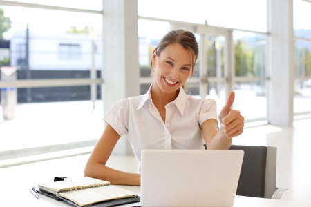 saleswomen: Cheerful office-worker showing thumbs up in front of laptop