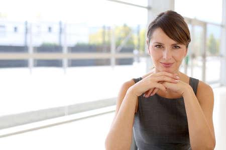 Retrato de mujer de negocios atractivo que se sienta en el edificio moderno