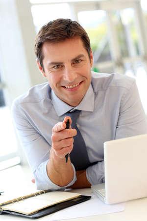 Happy Geschäftsmann sitzt im Büro