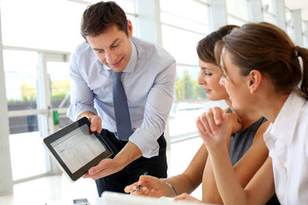 Manager presenting business plan with electronic tablet photo