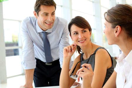 personas comunicandose: Grupo de hombres de negocios hablando alrededor de la mesa en la oficina Foto de archivo