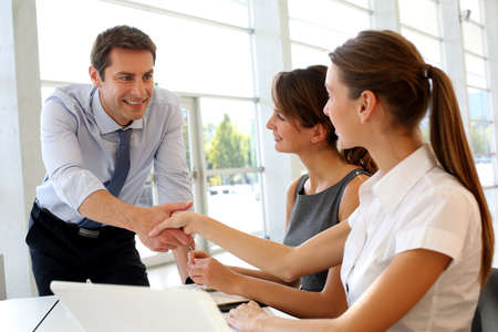 collaboration: Salesman shaking hands to clients