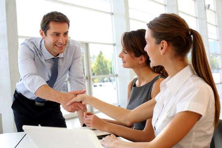 dandose la mano: Vendedor de dar la mano a los clientes Foto de archivo
