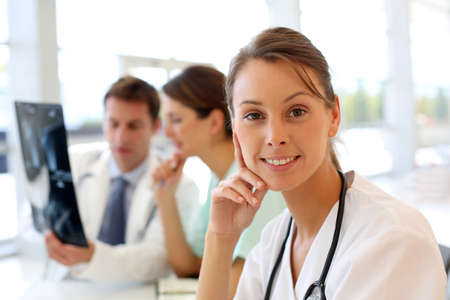 Portrait of beautiful nurse sitting in office, people in background Stock Photo - 15811260