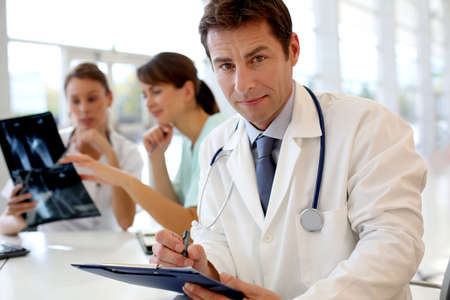 Portrait of doctor sitting in office, people in background Stock Photo - 15811287