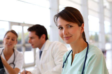 Attractive nurse working in hospital, people in background photo