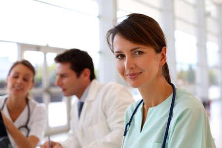pediatra: Enfermera atractiva que trabaja en el hospital, la gente en el fondo Foto de archivo