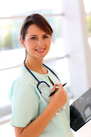 Smiling pediatrician standing in clinic hallway Stock Photo - 15811285