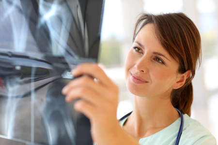 pediatra: Enfermeira olhando para os resultados de raios-X