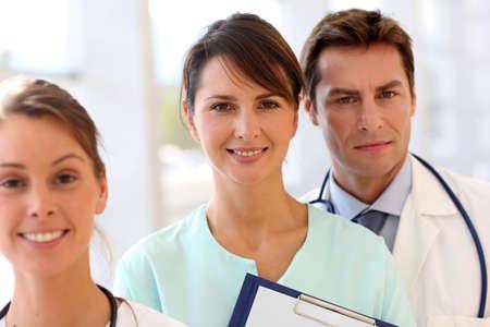 uniforme medico: Posici�n, sonriente, equipo m�dico en la sala de Foto de archivo