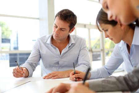 firmando: Los socios de negocios la firma de los documentos contractuales
