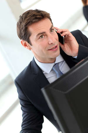 telephone salesman: Businessman in office talking on the phone