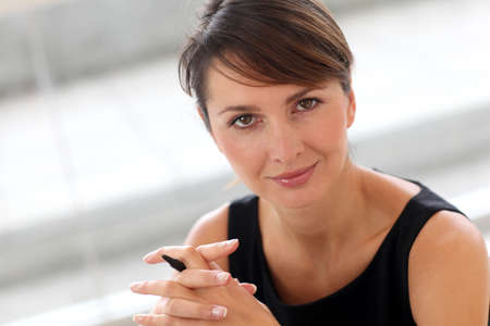 30 years old woman: Portrait of attractive businesswoman sitting in office Stock Photo