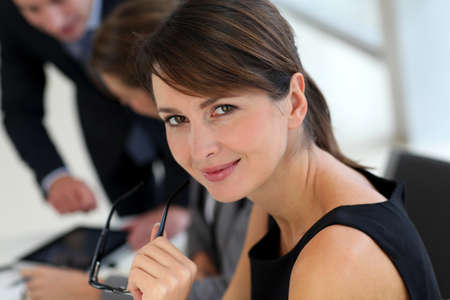 30 years old woman: Attractive businesswoman sitting in office with workteam