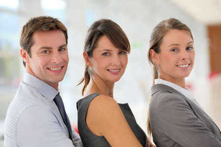 40s adult: Cheerful business team standing in hallway Stock Photo