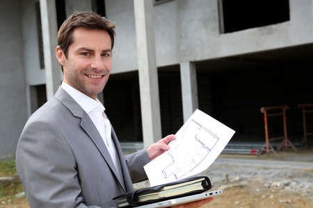 real estate agent: Construction salesman checking building site