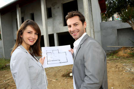 Couple on construction site checking building progress photo