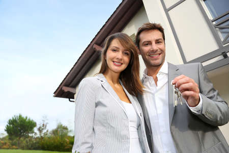 home keys: Couple in front of new home holding door keys Stock Photo