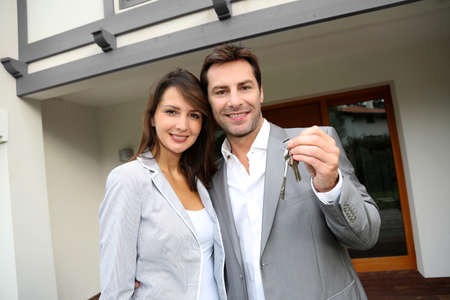 Couple in front of new home holding door keys photo