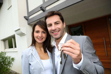 Home for sale: Couple in front of new home holding door keys Stock Photo