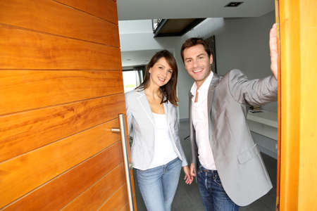Couple opening the front door of their home