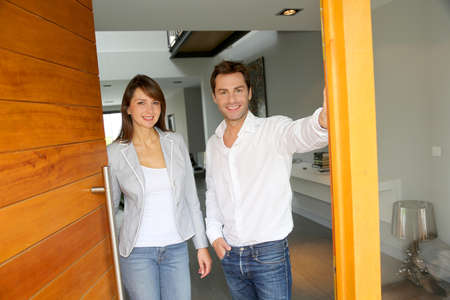 front door: Couple opening the front door of their home