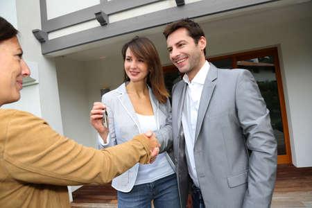 dandose la mano: Los nuevos due�os de propiedad d�ndose la mano al agente de ventas Foto de archivo